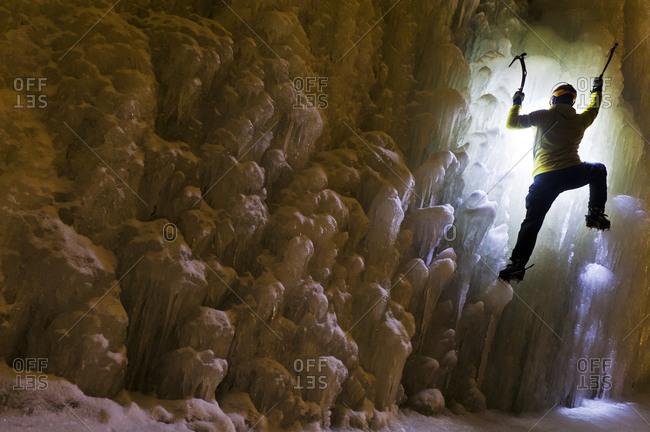 Man ice climbing up frozen waterfall adventure