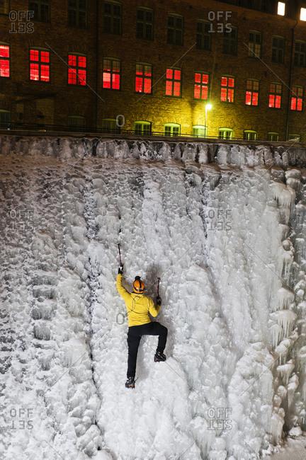 Man ice climbing up frozen waterfall in urban area adventure