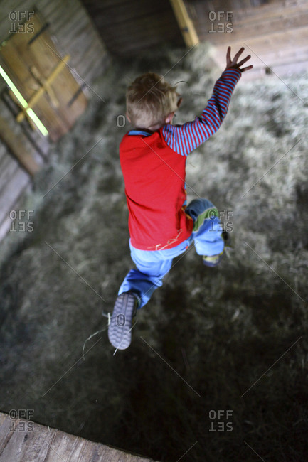 Child jumping on hay in barn