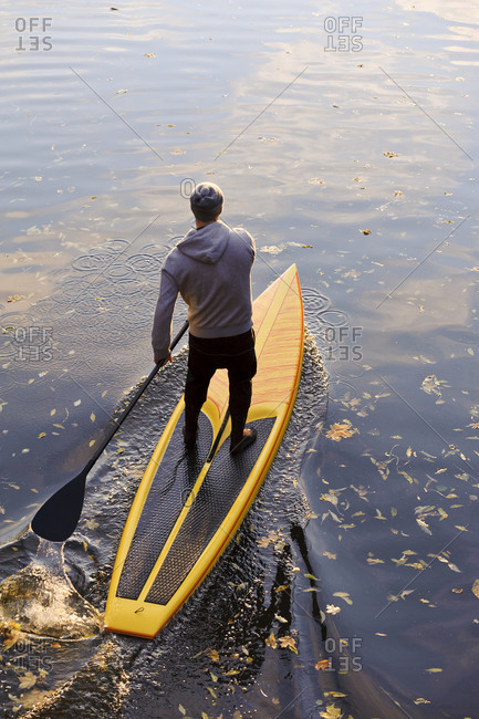 Man rowing paddle board in water, elevated view