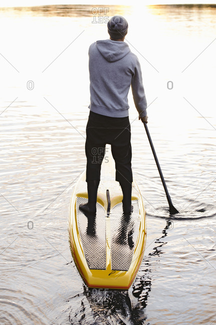 Man rowing paddle board in water, rear view