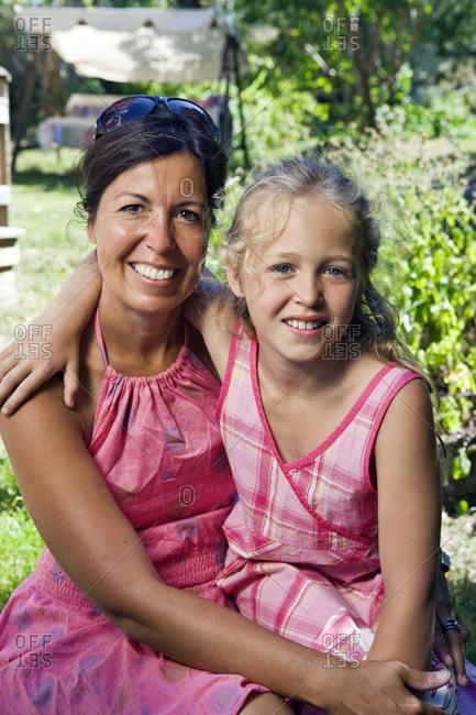 Portrait of mother with daughter in garden