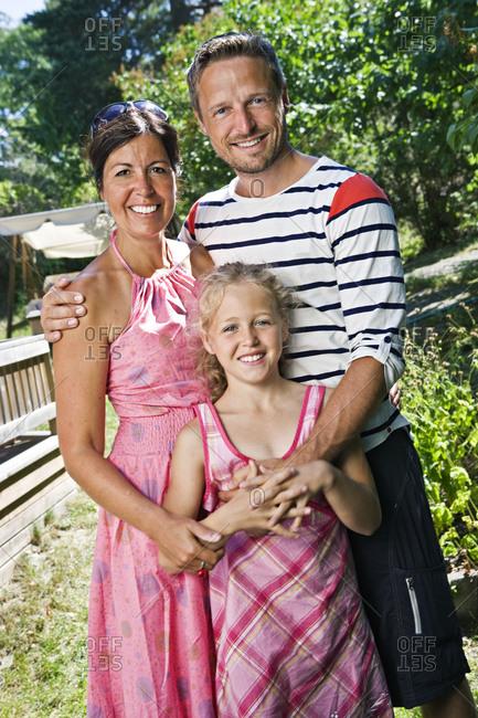 Portrait of parents with daughter in garden
