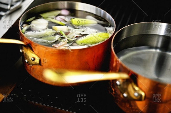 Copper pots of soup and water on a hob