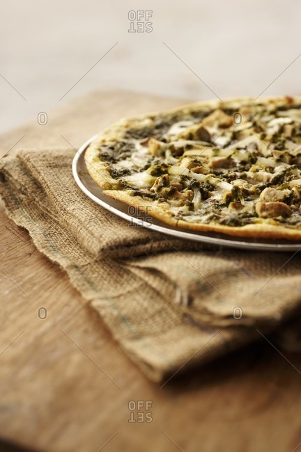 Thin Crust Pizza Topped with Chicken, Mushrooms, Onions and Pesto