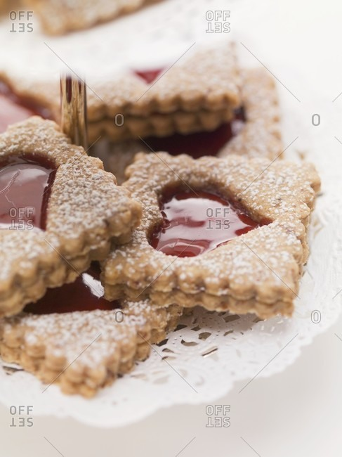 Jam biscuits with icing sugar on a cake stand