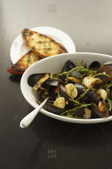 Bowl of Steamed Mussels with a Spoon; Grilled Bread Slices