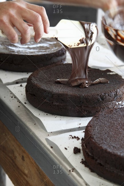 A chocolate cake being glazed