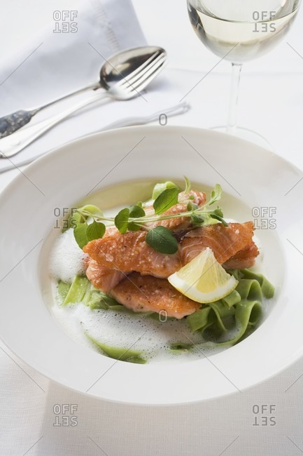 Salmon fillet on green ribbon pasta