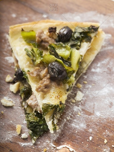 Two pieces of pizza with mince, olives, spinach and cheese