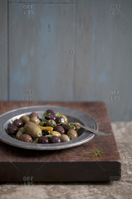 Mixed Marinated Olives with Thyme on a Metal Plate
