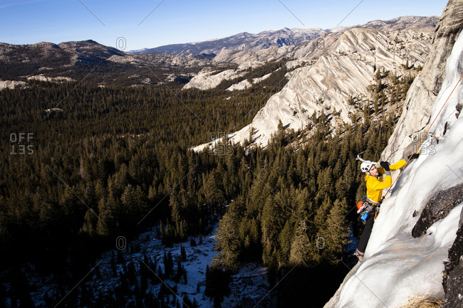 An ice climber climbs Yellow Brick Road (WI3+) on Drug Dome in Tuolumne Meadows located inside Yosemite National Park, California.