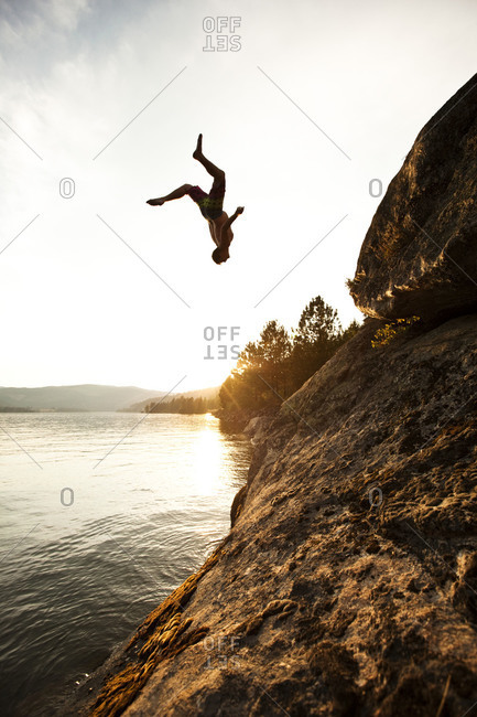 A athletic man flips off a cliff into a lake at sunset in Idaho.