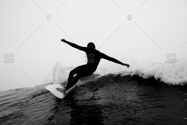 A male surfer rips a cutback while surfing at Leo Carillo Sate Beach in Malibu, California.