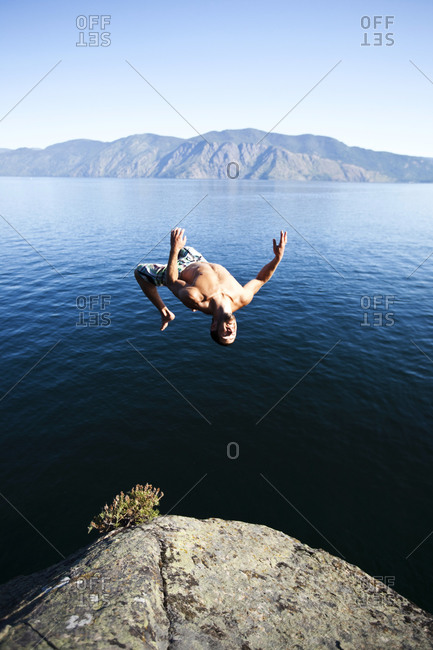 A young man back flips off a cliff into a lake in Idaho.