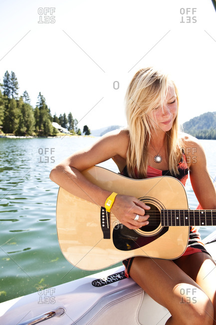 A beautiful young woman smiling plays the guitar on a wakeboard boat on a lake in Idaho.