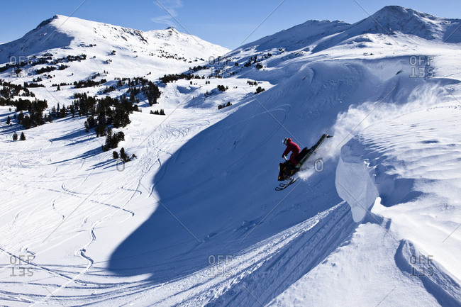 A snowmobiler jumping off a cornice on a sunny winter day in Montana.