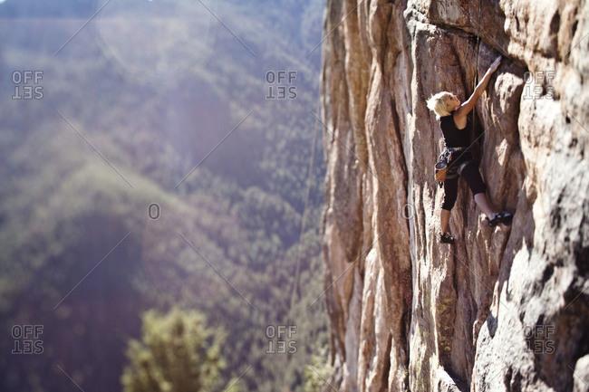 A athletic woman rock climbing near Bozeman, Montana.