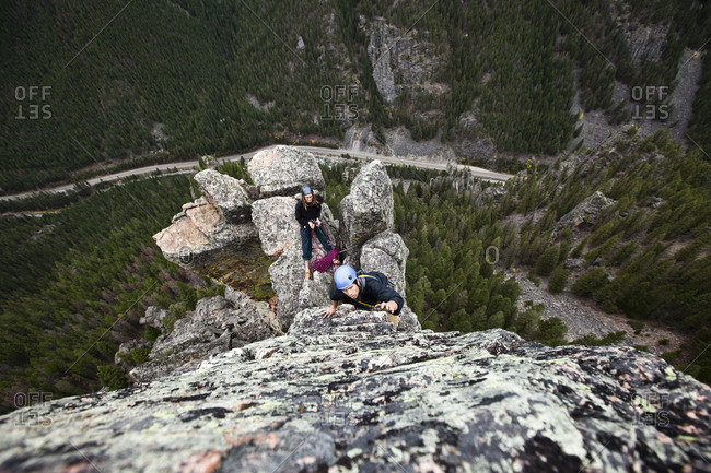 A young man rock climbing leads up a tower in Montana.