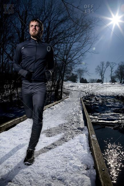 A man runs on a bridge over a creek in the snow.
