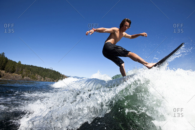 A athletic young man wakesurfing on a sunny day in Idaho.