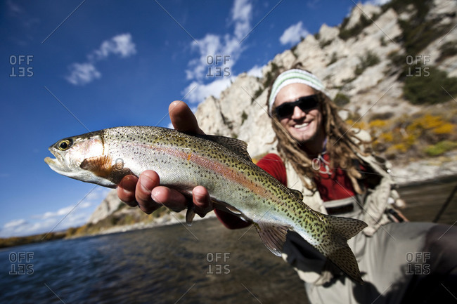 A male fly fisher holds a freshly caught rainbow trout out of a river in Bozeman, Montana.
