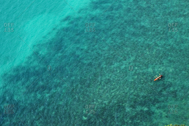A aerial view of a couple kayaking in turquoise water in Thailand.