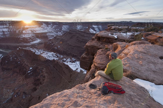 Male hiker watching the sunset from Dead Horse Point State Park, Moab, Utah.