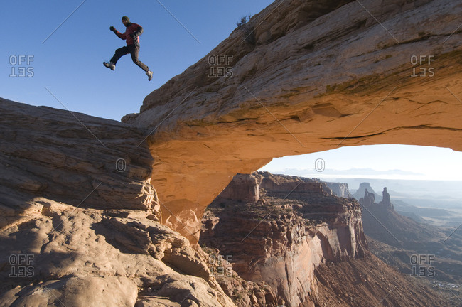 A male jumping off sandstone arch, Canyonlands National Park, Moab, Utah.