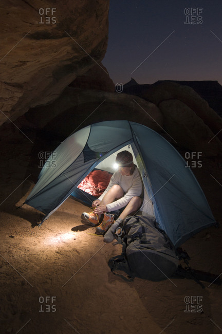 A woman camping in a tent with a headlamp in Indian Creek Canyon, Monticello, Utah.