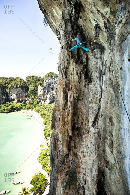 A athletic man rock climbing high above the beach on a multi pitch route in Thailand.