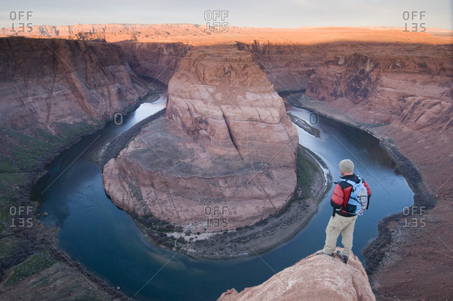 Male hiker watching the sunrise at the Horseshoe Bend Overlook with the Colorado River below, Page, Arizona.