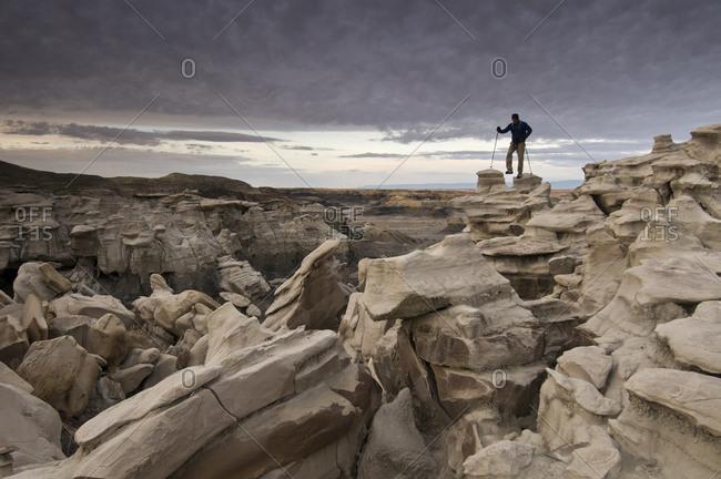 A man hiking through the complex sandstone rock formations at Bisti Badlands, Farmington, New Mexico.