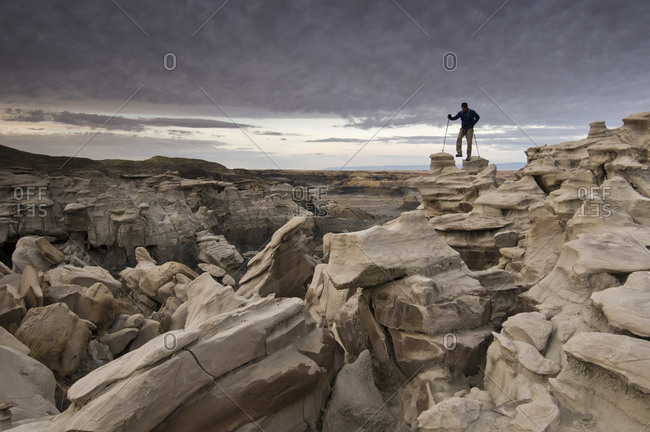 A man hiking through the complex sandstone rock formations at Bisti Badlands, Farmington, New Mexico.