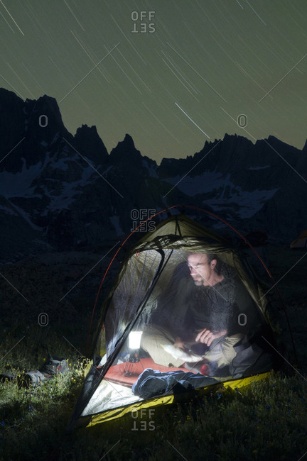 A male hiker in tent at night below the Cirque of Towers, Wind River Range, Pinedale, Wyoming.