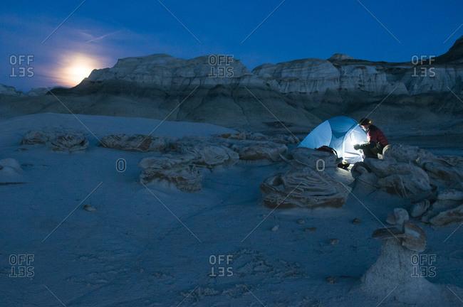 A man setting up a tent at night, Bisti Badlands, Farmington, New Mexico.