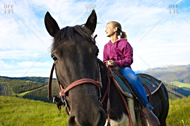 A girl sits in the saddle enjoys an early morning horseback adventure in a high alpine mountain Summer meadow.