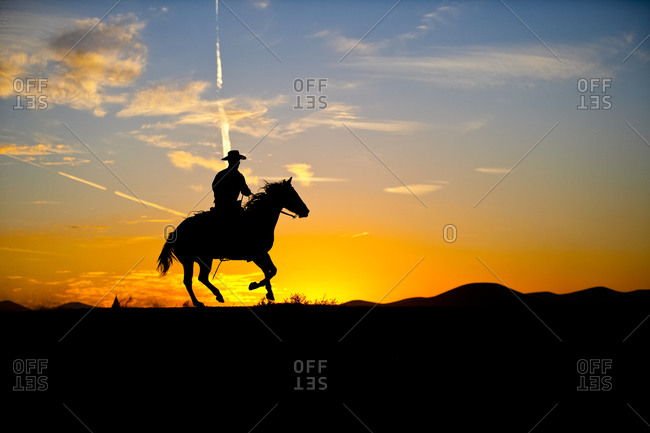 A silhouetted cowboy rides his mount along a ridge line as the sun sets behind him.
