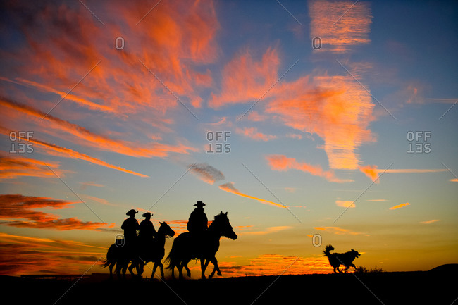 A silhouetted group of cowboys ride along a ridge line as the sun sets behind them.