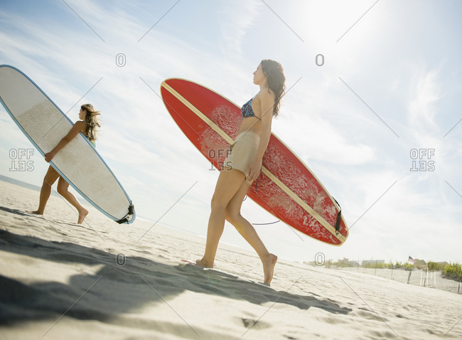 Two women carrying surfboards on beach