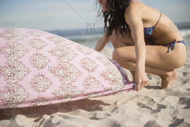 Woman preparing blanket on beach