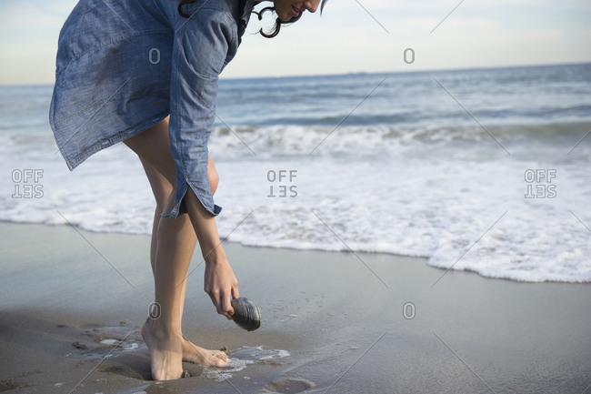 Woman collecting seashells on beach