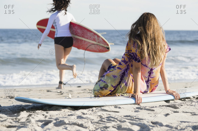 Two female surfers on beach