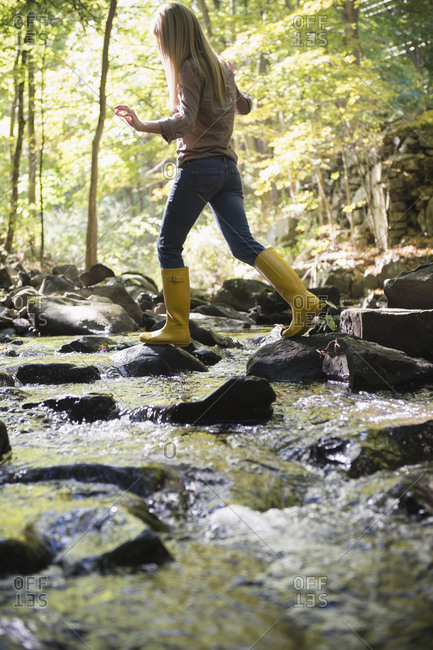 Woman walking on rocks in stream