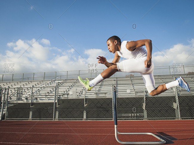 Boy (12-13) hurdling on running track