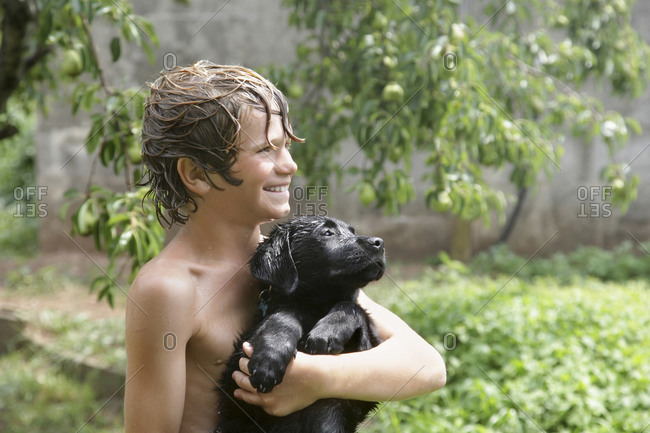Boy (10-11) with Labrador puppy playing with water