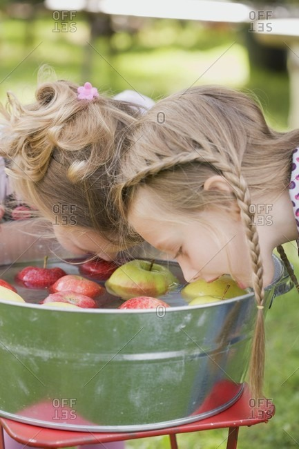 Two girls bobbing for apples