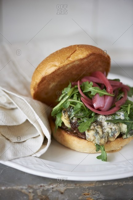 Blue Cheese Burger with Arugula and Pickled Onions on a Roll