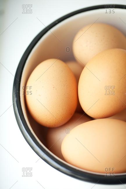 Raw, organic eggs in a white bowl