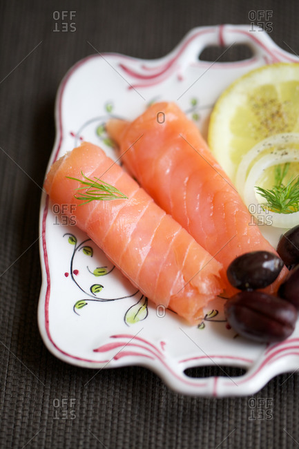Smoked salmon, olives, lemon, dill on a plate